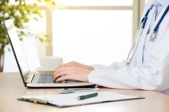 Доктор используя компьютер для того чтобы исследовать интернет, здравоохранение и сотрудник военно-медицинской службы Стоковая Фотография