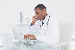 Доктор используя мобильный телефон и компьтер-книжку на медицинском офисе Стоковое Фото