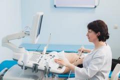 Доктор используя ультразвук и экранирующ живот беременной женщины Стоковое Изображение RF