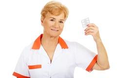 Доктор или медсестра улыбки пожилые женские держат волдырь пилюлек стоковое фото rf
