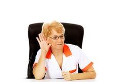 Доктор или медсестра улыбки пожилые женские сидя за столом и подслушивают переговор стоковое фото
