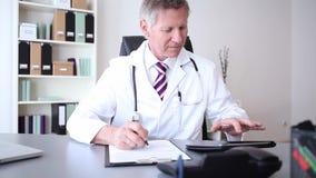 Доктор или практикующий врач с цифровой таблеткой пока пишущ примечания видеоматериал