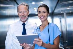 Доктор и коллега обсуждая над цифровой таблеткой Стоковые Изображения RF