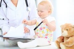 Доктор и пациент в больнице Маленькая девочка рассматривается педиатром с стетоскопом микстура здоровья внимательности стоковые изображения