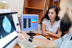 Доктор и пациент наблюдают маммограмму стоковые фотографии rf
