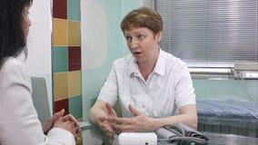 Доктор и пациент обсуждая в зале ожидания больницы стоковое фото