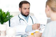 Доктор и пациент обсуждая что-то Стоковое Изображение