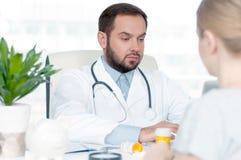 Доктор и пациент обсуждая что-то Стоковые Изображения RF