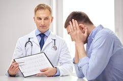 Доктор и пациент с cardiogram на доске сзажимом для бумаги Стоковое Фото