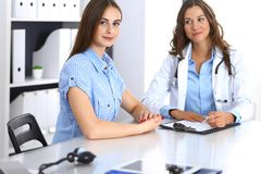Доктор и счастливый терпеливый говорить пока сидящ на столе Врач или терапевт обсуждая здоровое lifesty стоковые изображения rf