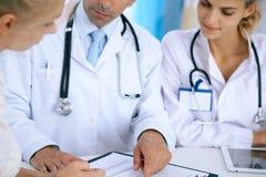 Доктор и терпеливый говорить пока сидящ на столе в офисе Врач указывая в форму истории болезни Medicin стоковая фотография