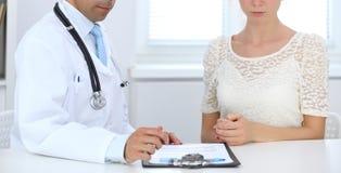 Доктор и терпеливый говорить пока сидящ на таблице Концепция поддержки и доверие в медицине стоковые фотографии rf