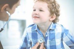 Доктор и терпеливый ребенок Мальчик врача рассматривая Регулярное медицинское посещение в клинике Медицина и здравоохранение стоковое фото rf