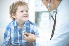 Доктор и терпеливый ребенок Мальчик врача рассматривая Регулярное медицинское посещение в клинике Медицина и здравоохранение стоковое изображение