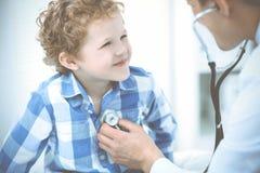 Доктор и терпеливый ребенок Мальчик врача рассматривая Регулярное медицинское посещение в клинике Медицина и здравоохранение стоковое фото