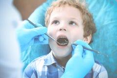 Доктор и терпеливый ребенок Мальчик имея его зубы быть расмотренным с медициной дантиста, здравоохранением и концепцией стоматоло стоковые фото