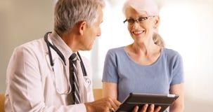 Доктор идя над пожилым файлом здоровья ` s женщины в офисе с таблеткой Стоковые Изображения RF