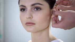 Доктор кладет глухую помощь на молодые ladys ухо, ухудшение слуха, работу для инвалидов стоковое изображение rf