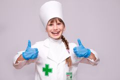 Доктор маленькой девочки в медицинских равномерных и голубых перчатках показывает большой палец руки вверх Стоковые Фотографии RF
