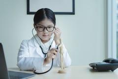 Доктор маленькой девочки рассматривая деревянную куклу стоковое изображение