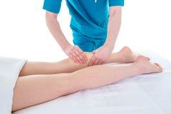 Доктор массажирует ногу женщины на встрече физиотерапии Стоковая Фотография RF