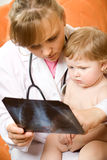 доктор младенца смотря рентгеновский снимок Стоковая Фотография