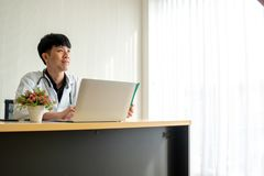 Доктор молодого человека читает терпеливую диаграмму и чувствует уверенным в его мысли на его работая столе стоковое изображение rf