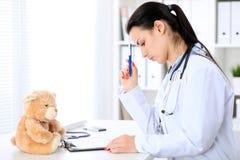 Доктор молодого брюнет женский сидя на таблице и работая компьютером на офисе больницы Доктор в тревоге Стоковые Изображения RF