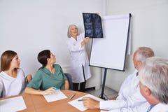 Доктор на встрече команды с изображением рентгеновского снимка Стоковые Фото