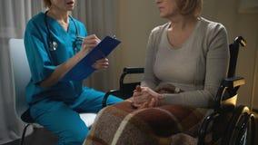 Доктор на звонке говоря к больной женщине в кресло-коляске и делая примечания, диагноз акции видеоматериалы