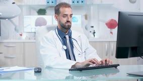 Доктор печатая на его компьютере после этого он пишет в доске сзажимом для бумаги сток-видео