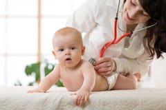 Доктор педиатра рассматривает младенца с стетоскопом проверяя сердцебиение стоковое фото rf