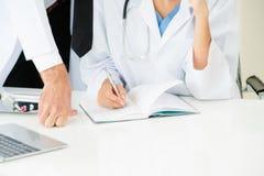 Доктор пишет отчет на столе с другим доктором стоковая фотография