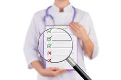 Доктор показывает лист бумаги для записывать, креста и контрольной пометки, изолированная предпосылка, лупа Стоковая Фотография RF