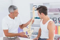 Доктор показывая анатомический позвоночник к его пациенту Стоковое Фото