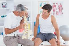 Доктор показывая анатомический позвоночник к его пациенту Стоковая Фотография RF