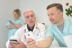 Доктор показывая телефон mobil к доктору Стоковое Изображение