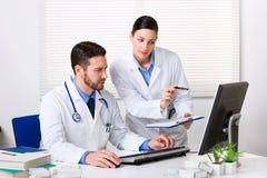 Доктор показывая что-то к коллеге Стоковая Фотография
