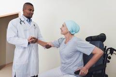 Доктор помогает женщине которое проходит реабилитацию после того как лечение рака получает вверх от кресло-коляскы стоковые изображения