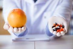 Доктор предлагая выбор между здоровой и витаминами Стоковые Фото