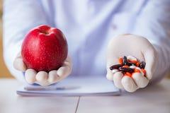 Доктор предлагая выбор между здоровой и витаминами Стоковая Фотография