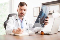 Доктор принимая примечания от некоторых рентгеновских снимков Стоковое Изображение