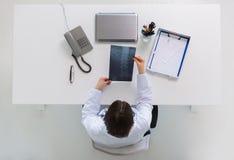 Доктор при рентгеновский снимок позвоночника сидя на таблице Стоковое Фото