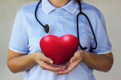 Доктор при стетоскоп держа красное сердце в крупном плане рук Стоковые Фото