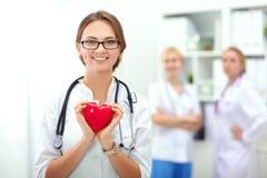 Доктор при стетоскоп держа сердце, изолированное на белой предпосылке Стоковое фото RF