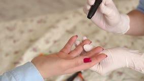 Доктор проверяет уровень глюкозы в крови девушки с glucometer сток-видео