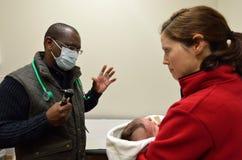 Доктор проверяет newborn младенца Стоковые Фотографии RF