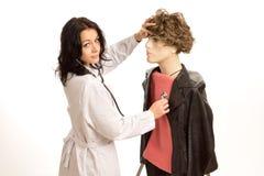 Доктор проверяя биение сердца куклы Стоковые Изображения