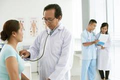 Доктор проверяя биение сердца пациента Стоковое фото RF