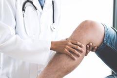 Доктор проверяя пациента с коленями для того чтобы определить причину беды стоковые изображения